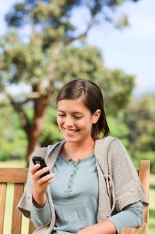 Jeune femme téléphonant sur le banc