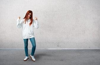Jeune fille rousse dans un sweat-shirt blanc urbain avec des lunettes célébrant une victoire