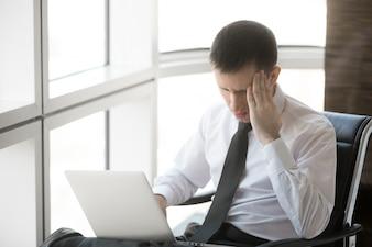 Jeune homme d'affaires ayant le mal de tête