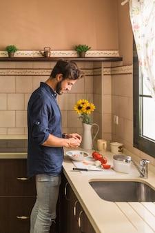 Jeune homme, debout, cuisine, préparation, salade