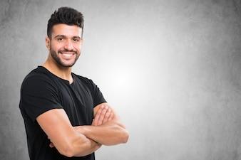 Jeune homme souriant devant un mur de béton