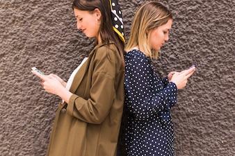 Jeunes amies debout dos à dos à l'aide de téléphone portable
