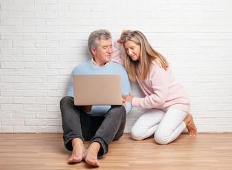Joli couple de personnes âgées assis sur le sol de leur maison avec un ordinateur portable