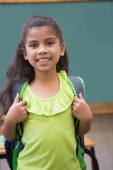 Jolie élève souriant à la caméra dans la salle de classe