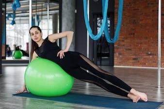 Jolie jeune femme flexion muscles abdominaux sur la balle verte dans la salle de gym