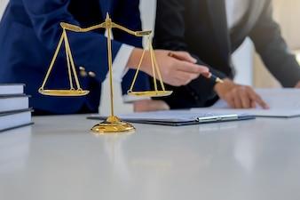 Juge marteau avec les avocats de la Justice ayant une réunion d'équipe dans un cabinet d'avocats en arrière-plan.