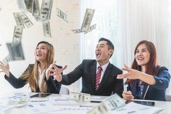 L'équipe des affaires lance de l'argent pour le concept de succès financier commercial au bureau