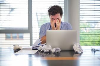 L'homme a l'air fatigué tout en travaillant
