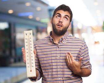L'homme avec la chaleur tenant un gros thermomètre