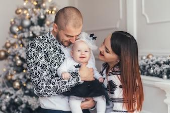 La mère et le père embrassant leur fille et se tenant près de l'arbre de Noël