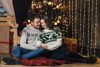 Le charmant couple amoureux assis près de sapin de Noël