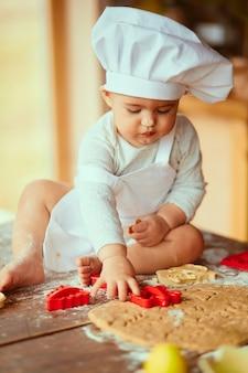 Le petit bébé est assis sur la table près de la pâte
