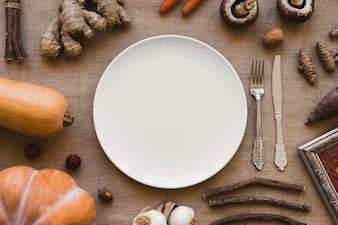 Légumes et bâtonnets autour de la plaque et de la coutellerie