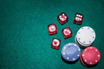 Les dés rouges et les jetons de casino s'empilent sur une table de poker verte