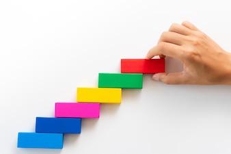 Les femmes à la main mettent un bloc de bois rouge sur des blocs de bois colorés en forme d'escalier.