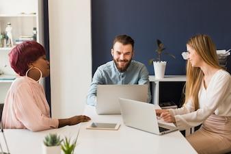 Les gens avec des ordinateurs portables au bureau