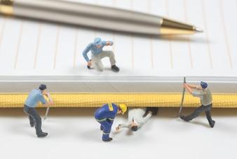 Les gens en miniature essaient d'aider les gens qui ont été écrasés par un cahier et un stylo