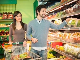 Les gens qui prennent des légumes dans un supermarché