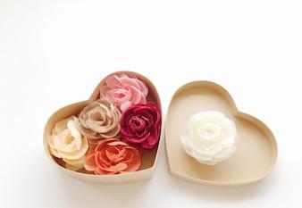 Les roses de couleur fleurissent dans une boîte en forme de coeur.
