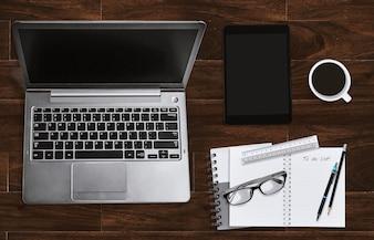 Lieu de travail de bureau avec ordinateur portable et ordinateur portable avec des lunettes et une tablette. Vue de dessus.