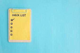 Liste de contrôle papier sur presse-papiers en bois sur le fond bleu