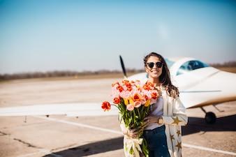 Magnifique brune se dresse avec un grand bouquet de tulipes devant un avion