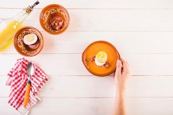Main avec une assiette à soupe sur la table de cuisson