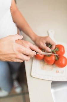 Main de culture aidant la femme à couper les légumes