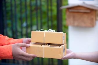 Main de femme acceptant une livraison des boîtes marron du concept de livraison livreur