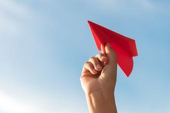 Main de femme tenant une fusée de papier rouge sur fond de ciel bleu