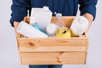 Main de l'homme avec une boîte en bois pleine de bouteilles et de boîtes de conserve