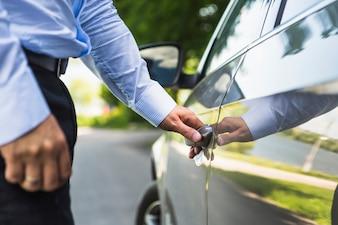 Main de l'homme ouvrant la porte de la voiture