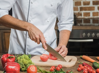 Main du chef couper la tomate mûre en tranches sur la planche à découper