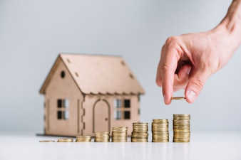 Main humaine empiler des pièces de monnaie devant un modèle de maison