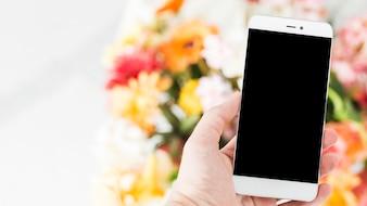 Main humaine sur téléphone portable avec bouquet de fleurs en arrière-plan