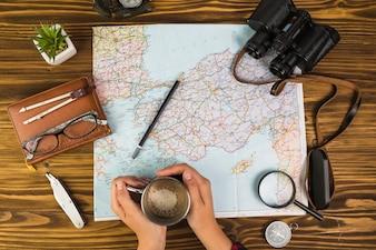Main humaine tenant la tasse de café avec des équipements de voyage sur le bureau