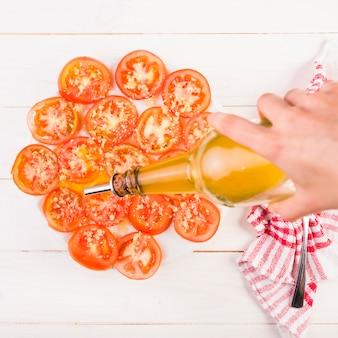 Main mettre l'huile sur une assiette de tomates