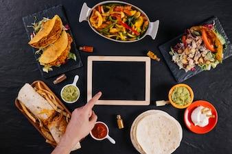 Main, pointant sur tableau noir au milieu de la nourriture mexicaine