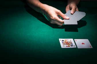 Main tenant des cartes de poker sur la table de casino