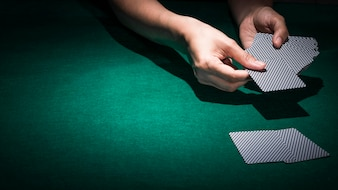 Main tenant une carte de poker sur la table de casino verte