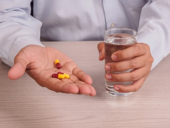 Mains de l'homme avec des pilules et un verre d'eau