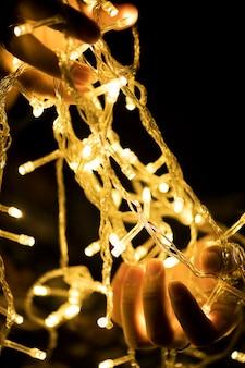 Mains tenant des lumières de décoration de guirlande