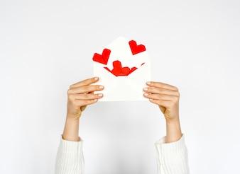 Mains tenant l'enveloppe avec des coeurs à l'intérieur sur fond blanc