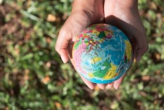 Mains tenant le globe de boule dans la mise au point sélective, éléments de cette image fournis par la NASA.