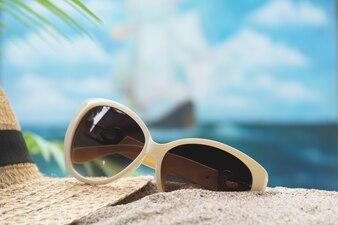 Matériel de voyage, lunettes et chapeau de soleil sur fond de ciel et mer.