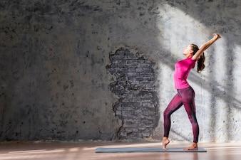 Mince jeune femme pratiquant des exercices d'étirement contre un mur patiné