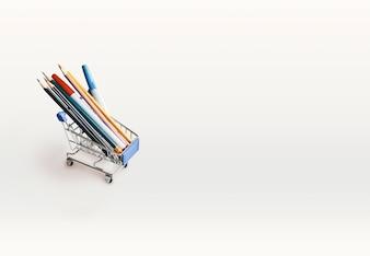 Mini chariot avec des crayons, des stylos sur une table blanche avec espace de copie. Vue de dessus.