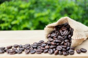 Mokka grains de café dans le sac sur la planche de bois, près du fond des jardins.