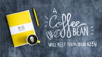 Mug avec grains de café avec ampoule sur le livre de grandes idées et texte sur tableau noir