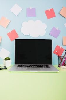 Mur avec papier nuage et notes adhésives derrière un ordinateur portable avec écran noir